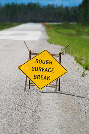 A yellow rough surface break sign with a road blurring into the background.