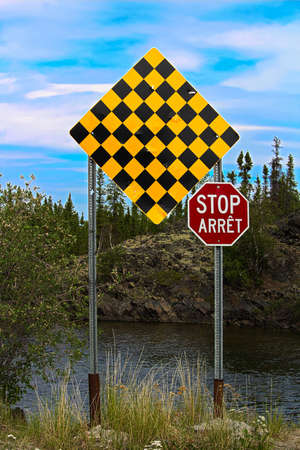 A checkered no entry and stop sign in both english and french.
