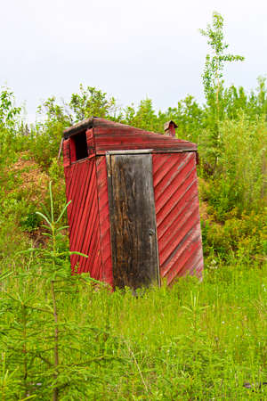 A red outhouse along a hiking trail. Stock Photo