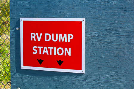 An RV dump station sign on the edge of a building.