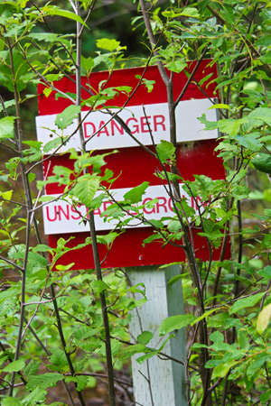 A danger, unstable ground sign obscured by trees. 免版税图像
