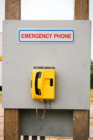 An emergency phone located on a wooden billboard.