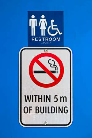 door handle: A no smoking within 5m of building sign at a reststop washroom. Stock Photo