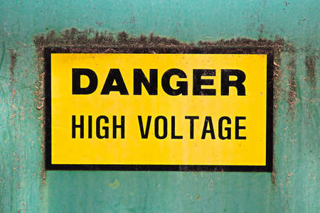 A danger high voltage sign on a green background.