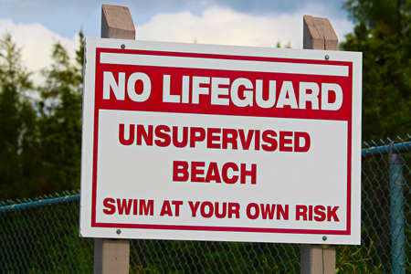 A no lifeguard unsupervised beach use at own risk sign.