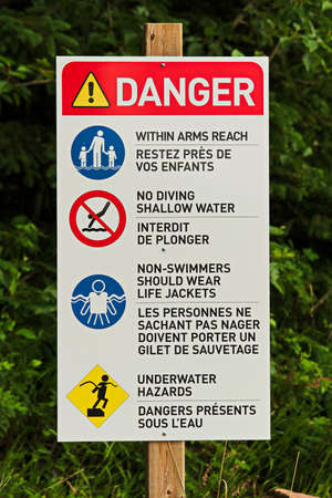 A danger sign with various beach rules on it.