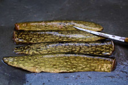 Closeup of the skin on a northern pike with a knife blade to the side. Stock Photo