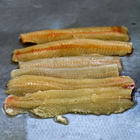 Six fillets of northern pike on a metal table.