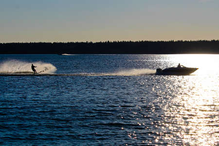 A boat and water skier silhouetted against a blue lake.