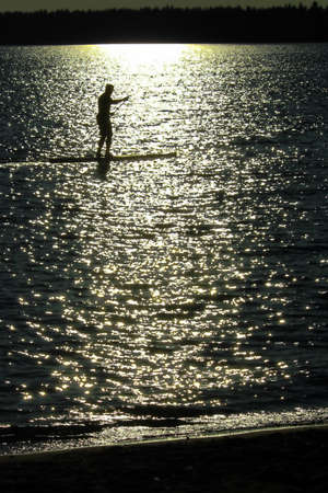 A silhouetted man paddle boarding on a Saskatchewan lake. Stock Photo