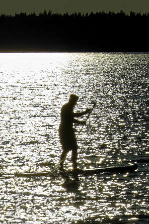 Closeup of a silhouetted man paddle boarding on a Saskatchewan lake.