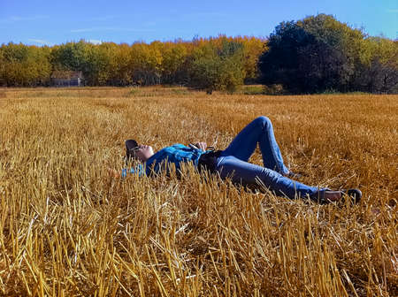 A young girl taking a break while working on a farm, laying down in a straw field looking up at the sky.