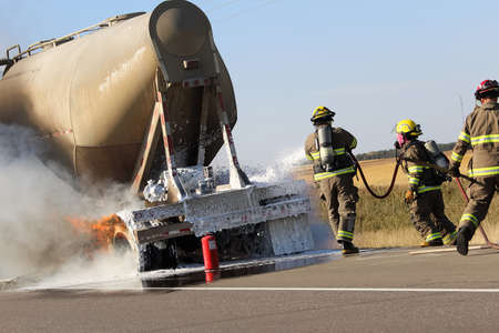 Three fireman rush to put out a brake fire on a semi-truck. Stock Photo