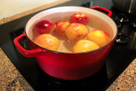 Peaches being boiled in a pot so the skins can be removed.