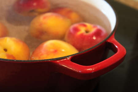 Closeup of a red pot handle while blanching peaches.