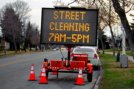 A street cleaning billboard with times in spring. Imagens
