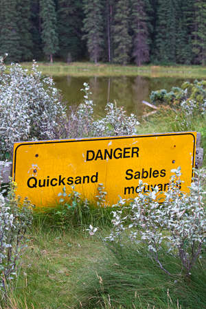A danger quicksand sign with a pond in the background.