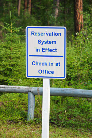 A reservation system in effect sign, check in at office. Stock Photo