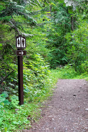 A washroom sign along a path pointing into the forest.