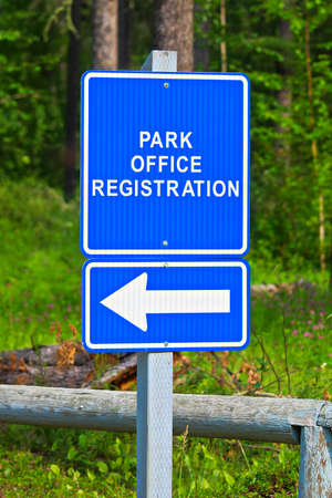 A blue park office registration direction sign.