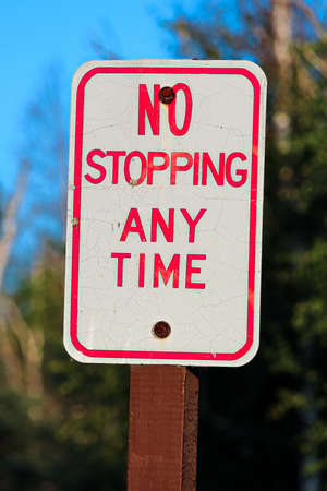 A red no stopping any time sign.