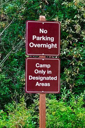 No parking overnight, camp in designated areas sign.