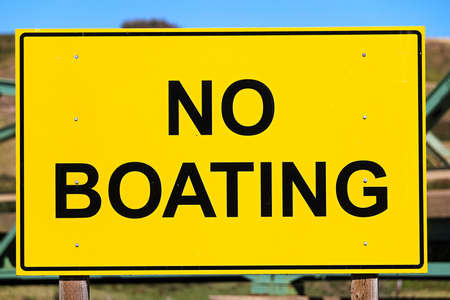 Closeup of a yellow no boating sign. Stock Photo