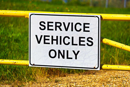 A service vehicles only sign on a metal gate.