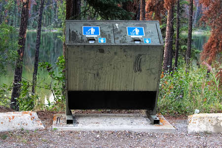 A bear proof garbage container along side a parking lot.