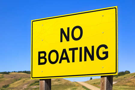 A yellow no boating sign against a blue sky. Stock Photo