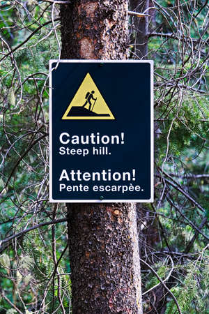 A caution steep hill sign on a edge of a trail.