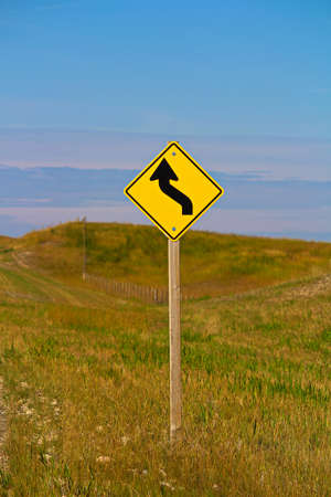 A curve ahead warning sign in the country.