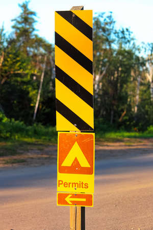 A permits sign with an arrow at a campground.