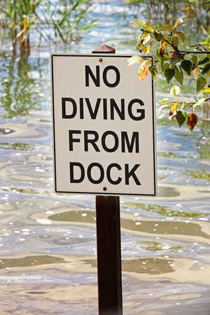 Closeup of a no diving from dock sign.