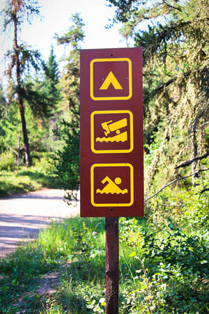 A camping, boat launch and swimming sign.
