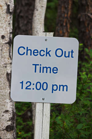 A sign indication check-out time is 12:00 pm.