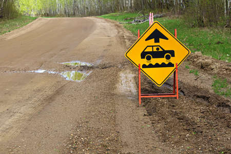 A bumpy road ahead sign with a large pothole. Stock Photo