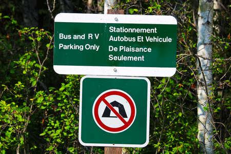 A bus and RV parking only sign in french and english.