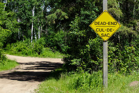 A Dead End sign beside a gravel road