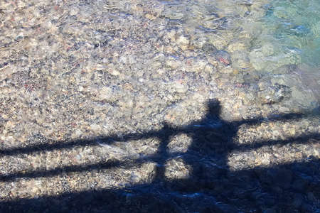Shadow of an individual on a bridge looking at the water Stock Photo