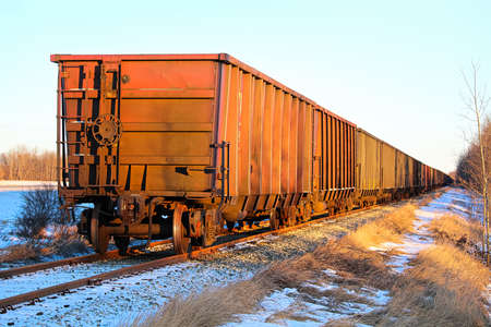 A train sitting on a track with golden sunlight on it Stock Photo