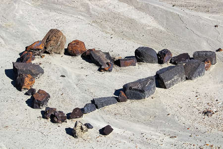 A set of rocks in the shape of a heart in the dried mud.
