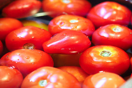 Closeup of various tomatoes being washed in water.