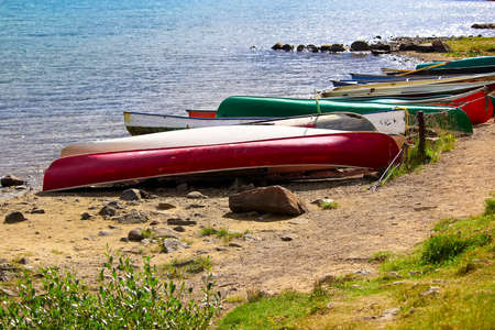 Various canoes chained up on a sandy shore.