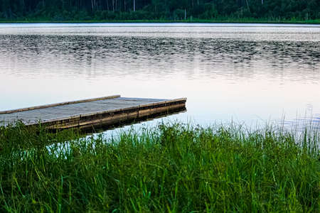 A boat dock at a quiet summer lake.