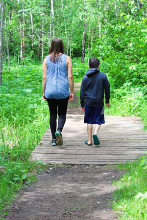 A young girl and boy take a walk in the forest Stock Photo
