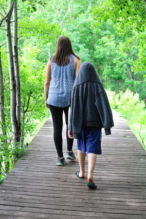 A young boy following a girl on a boardwalk on a tail Stock Photo