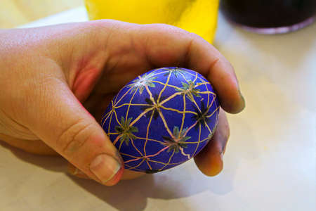 Holding a blue easter egg still covered in beeswax