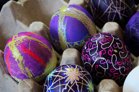 An egg carton holding decorated easter eggs
