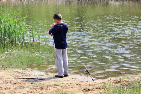 A boy getting his hook ready for fishing